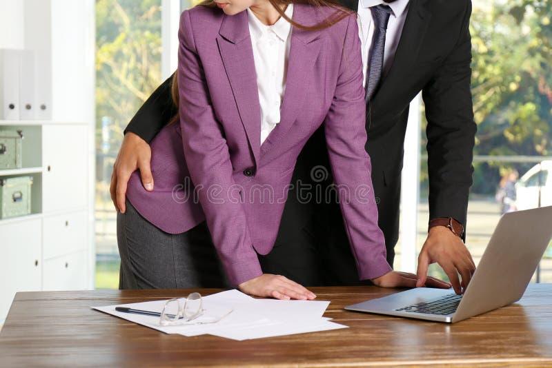 Chef- lastig vallend zijn vrouwelijke secretaresse in bureau stock foto's