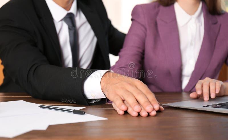 Chef- lastig vallend zijn vrouwelijke secretaresse in bureau, close-up stock fotografie