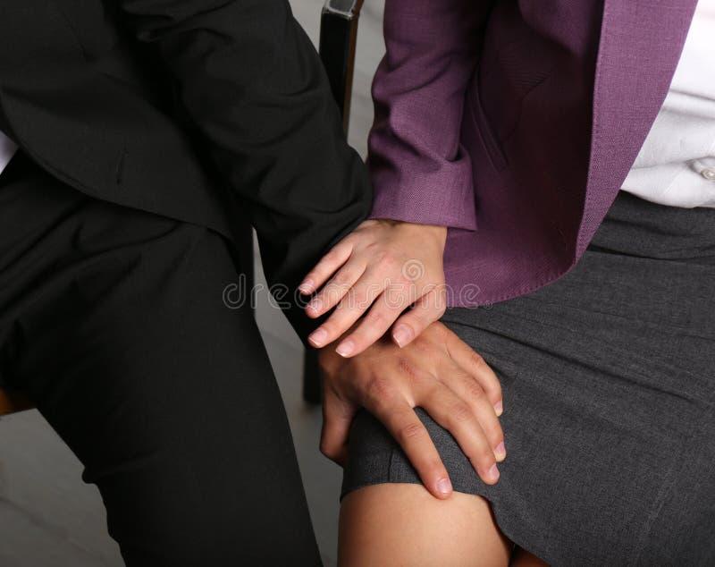 Chef- lastig vallend zijn vrouwelijke secretaresse in bureau, close-up stock afbeelding
