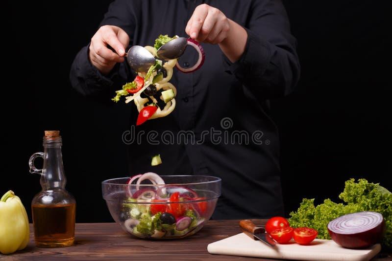 Chef mélangeant d'une manière ordonnée la salade fraîche d'été dans une cuvette Procédé de cuisson photo stock