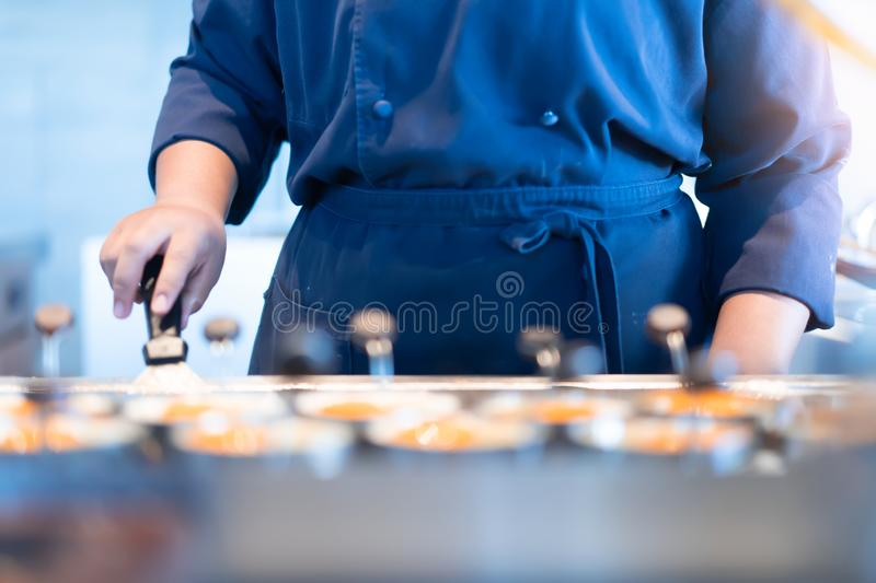 The chef is making fried eggs for breakfast. Worker for cooking at hotel concept royalty free stock photo