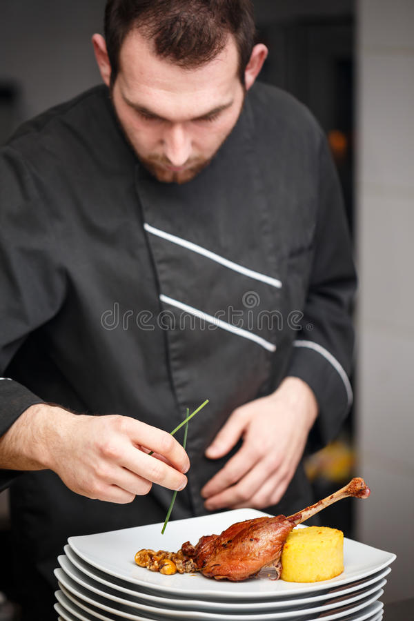 Chef is making meat dish. On commercial kitchen stock image