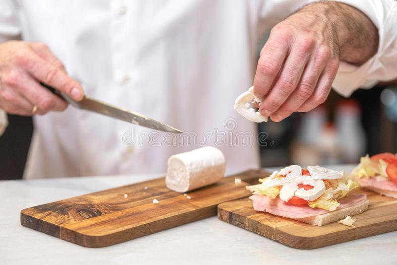 Chef making sandwich in rustic style with ham fresh vegetables and goat cheese. Delicious food. royalty free stock photography