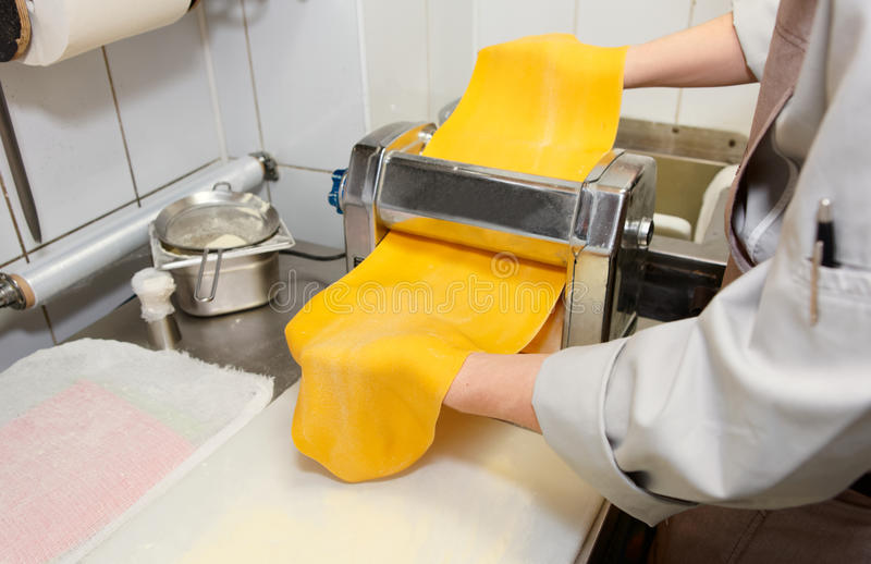 Chef is making thin dough. With special machine royalty free stock photo