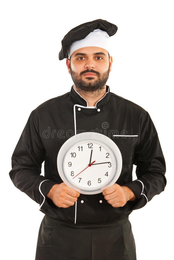 Chef male holding clock. Chef male in black uniform holding clock isolated on white background stock photo