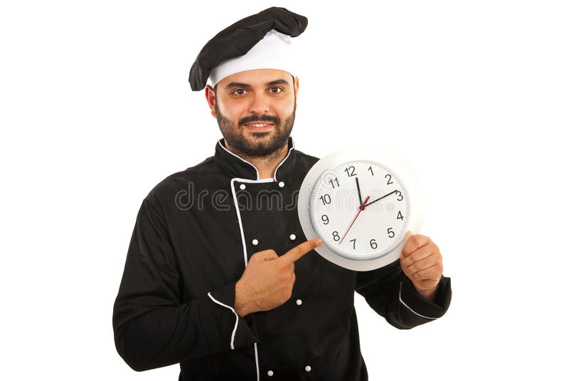 Chef male pointing to clock. Chef male in black uniform pointing to big clock isolated on white background royalty free stock image