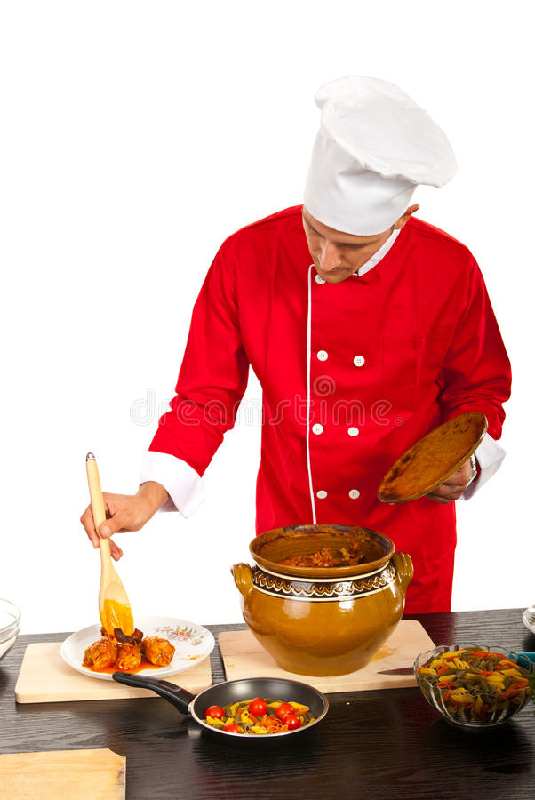Chef male put food on plate. Chef male putting food on plate in kitchen stock photo