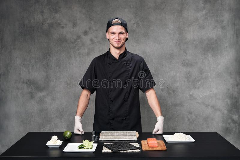 Chef man in the kitchen at the restaurant. Ingredients for sushi and rolls. stock photos
