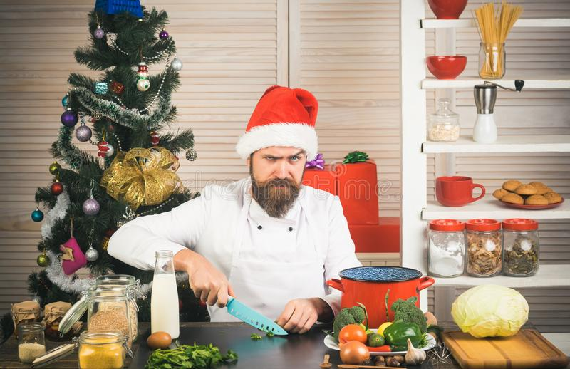 Chef man in santa claus hat cooking. stock photography