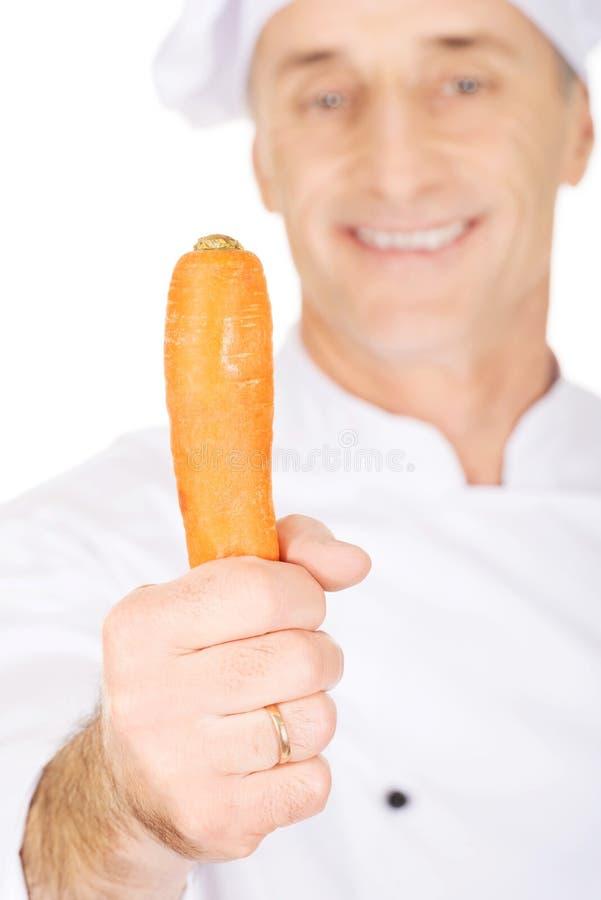 Chef masculin avec une carotte photographie stock