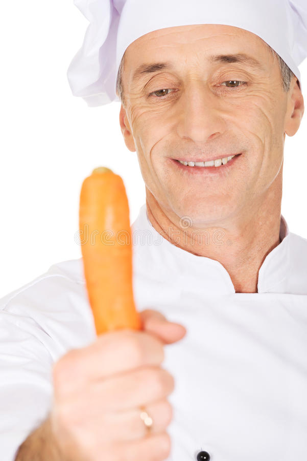 Chef masculin avec une carotte images stock