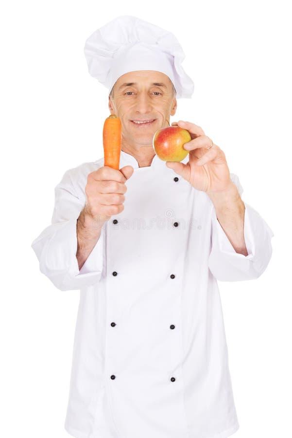 Chef masculin avec une pomme et une carotte photo stock