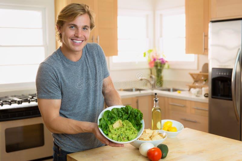 Chef masculin beau tenant un bol frais de guacamole fait maison organique photographie stock