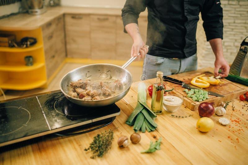 Chef masculin faisant cuire la viande avec des vetables dans la casserole images libres de droits