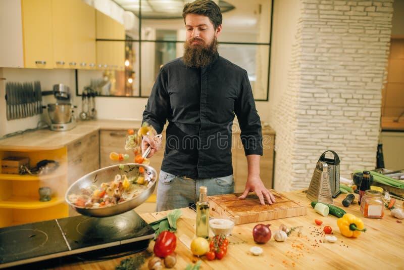 Chef masculin faisant cuire la viande avec des vetables dans la casserole photos stock