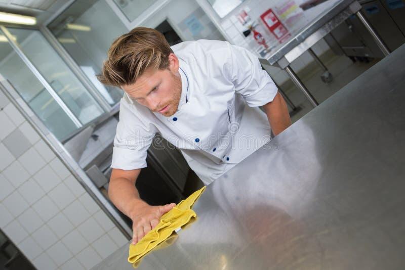 Chef masculin nettoyant la surface de travail de cuisine d'acier inoxydable images stock