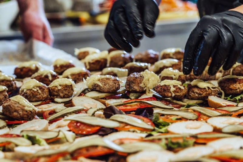 Chef masculin Putting Ingredients des hamburgers sur une diffusion découpée en tranches de pain sur un Tableau dans les gants noi images libres de droits