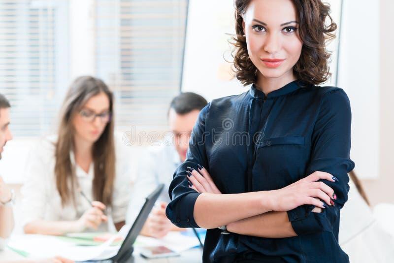 Chef med hennes lag som arbetar i kontoret arkivbild