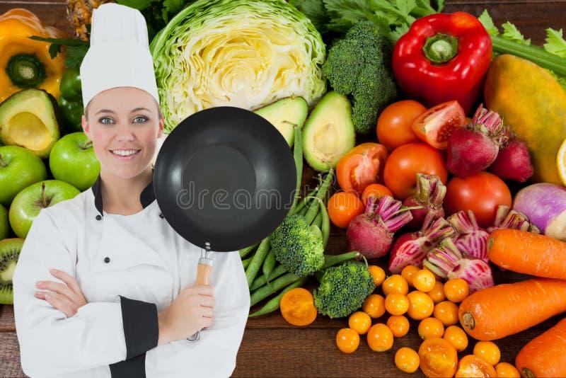 Chef med stekpannan mot grönsakbakgrund arkivbilder
