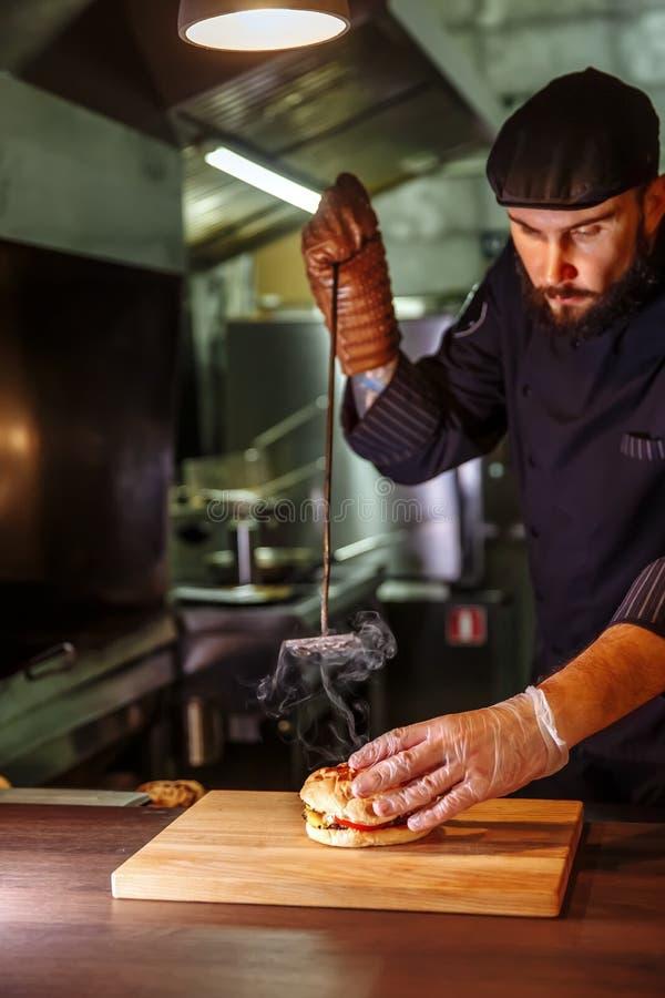 Chef mettant le petit pain sur le dessus, il faisant un hamburger de boeuf pour l'ordre de client image stock