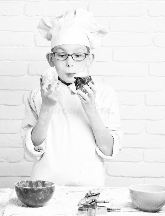 Chef mignon de cuisinier de jeune garçon dans l'uniforme et le chapeau blancs sur la farine souillée de visage avec des verres te photo stock