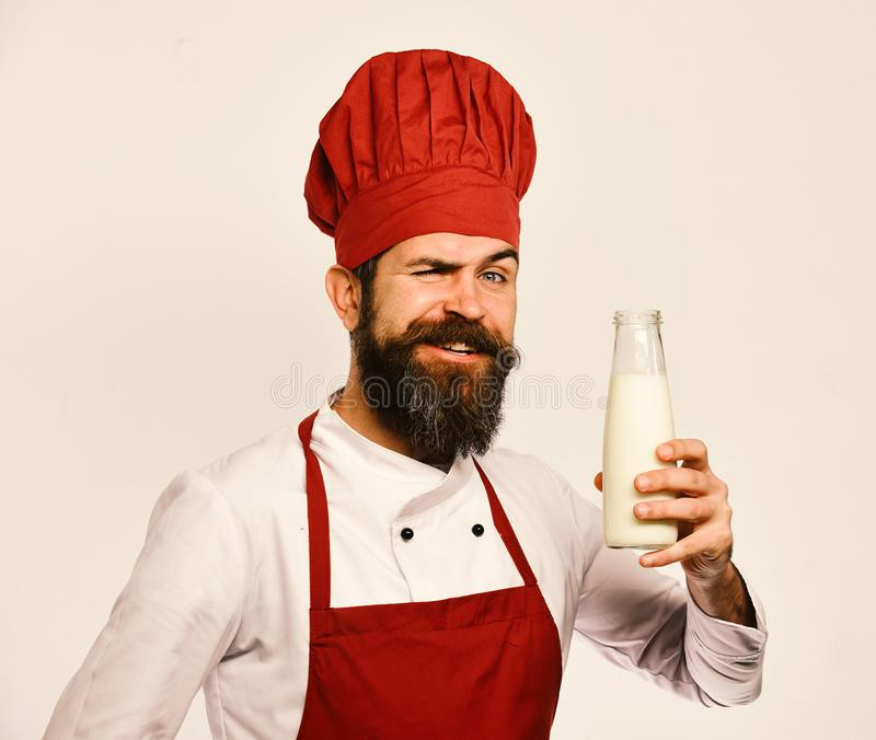 Chef with milkshake or yoghurt. Homemade food concept. Cook with flirty smile in burgundy uniform has liter of fresh milk. Man with beard holds bottle of milk royalty free stock images