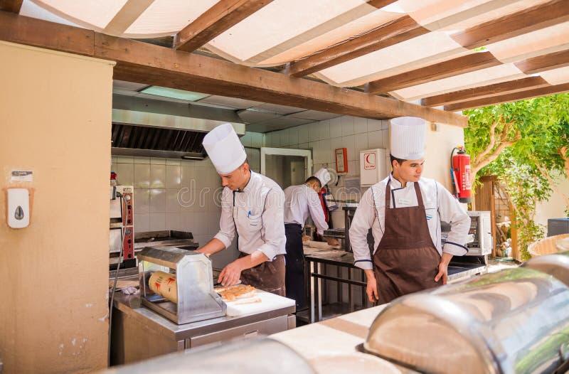 Chef mit Assistenten in der Küche stockfotos