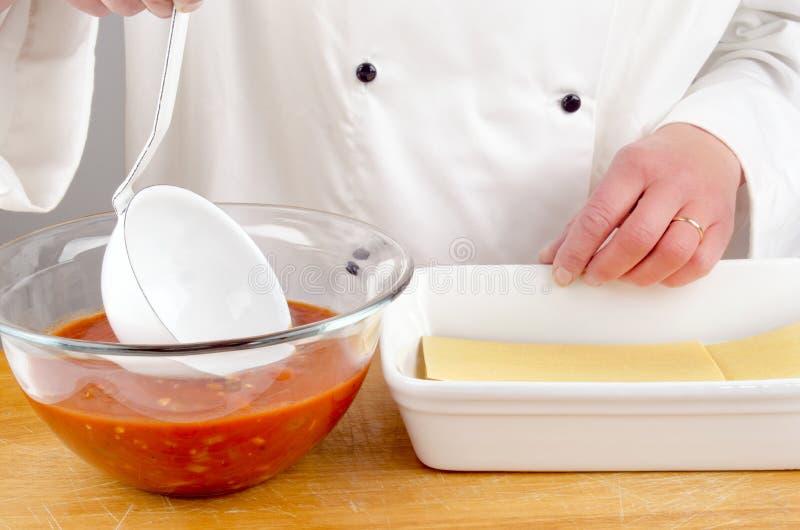 Chef mit der Tomatensauce, die Lasagne zubereitet stockbild