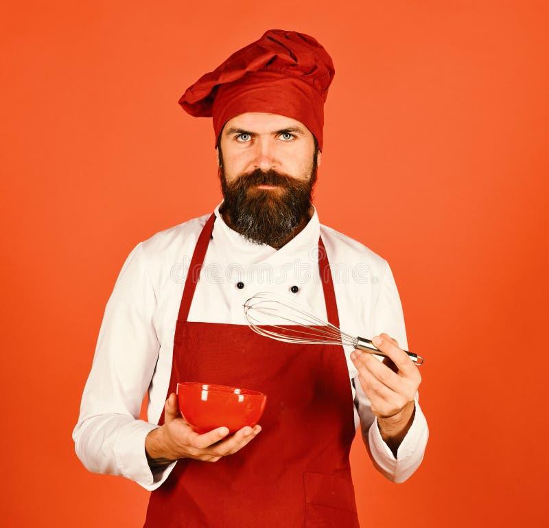 Chef mit Platte und peitschen Gerät Koch mit ernstem Gesicht lizenzfreie stockfotos