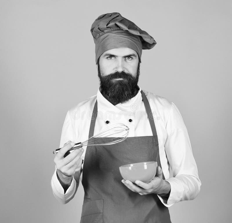 Chef mit Platte und peitschen Gerät Koch mit ernstem Gesicht lizenzfreies stockfoto