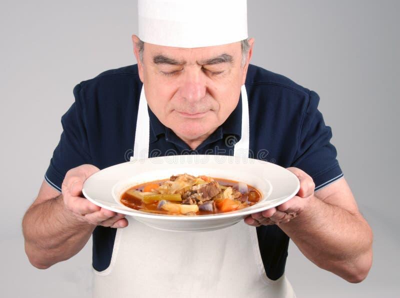 Chef mit Rindfleisch-Eintopfgericht lizenzfreie stockbilder
