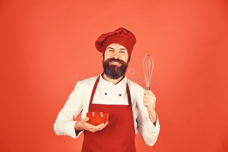 Chef mit roter Platte und peitschen Gerät Küche bearbeitet Konzept stockfoto