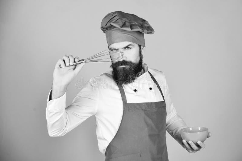 Chef mit roter Platte und peitschen Gerät Mann oder Hippie mit Bart hält Küchengeschirr auf rotem Hintergrund Set Hilfsmittel für lizenzfreie stockbilder