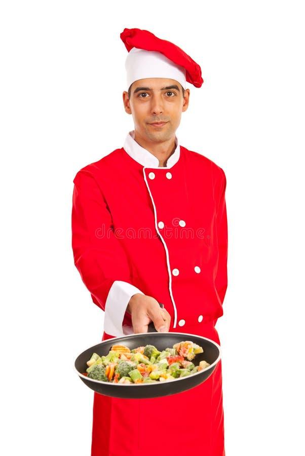 Chef montrant des légumes dans la poêle image stock