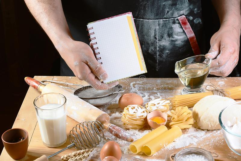 Chef with notepad text, ngredients for dough, cooking pasta tagliatelle spaghetti, including flour, eggs, milk, on wooden rustic b royalty free stock photos