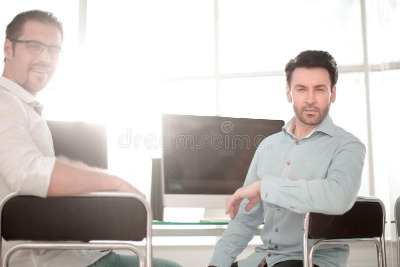 Chef och anställd som sitter nära skrivbordet royaltyfria foton