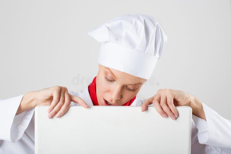Chef- oder Bäckerfrau, die unbelegtes leeres Anschlagtafelzeichen zeigt lizenzfreie stockfotografie