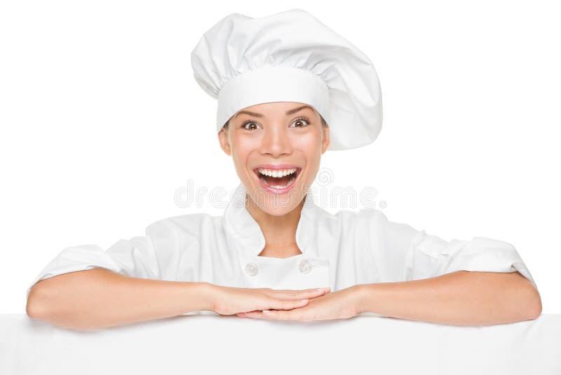 Chef- oder Bäckerfrau, welche die Zeichen-Anschlagtafel erregt zeigt lizenzfreie stockfotografie