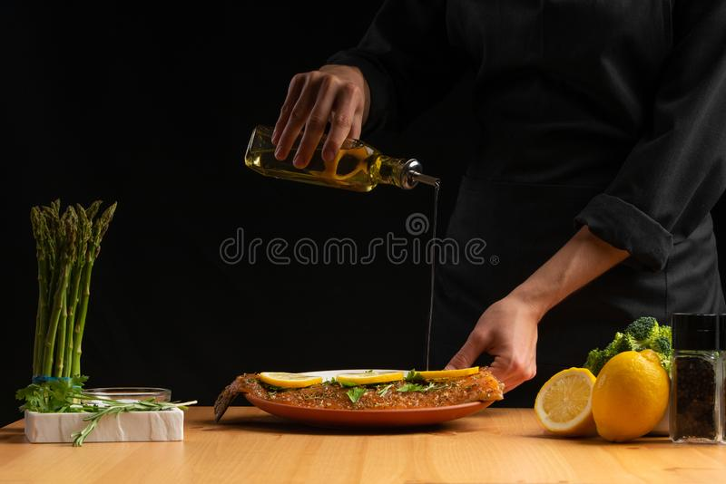 Chef oiling seafood, red salmon or trout fish, freezing in motion, Asian cuisine, recipe book, on black background. Preparing. Tasty and healthy food stock image