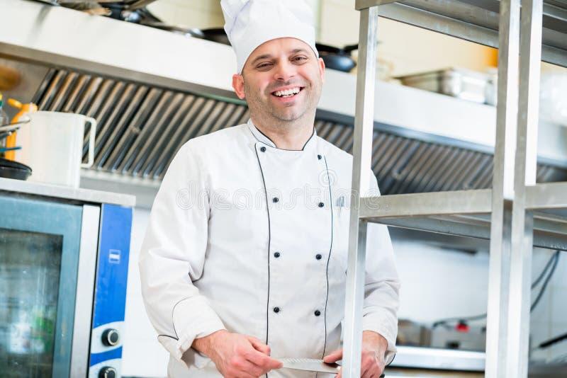 Chef ou cuisinier dans la cuisine d'hôtel faisant cuire des plats photos libres de droits