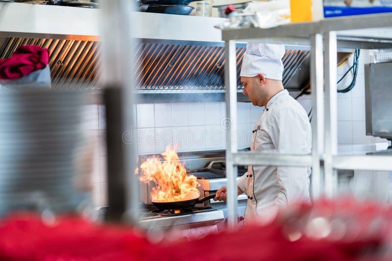 Chef ou cuisinier dans la cuisine d'hôtel faisant cuire des plats photographie stock libre de droits