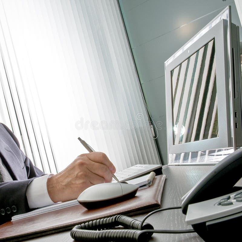 Chef på arbete Den sakkunniga handen av en affärsman som sitter på hans skrivbord, rymmer han pennan framme av hans datorbildskär royaltyfri bild
