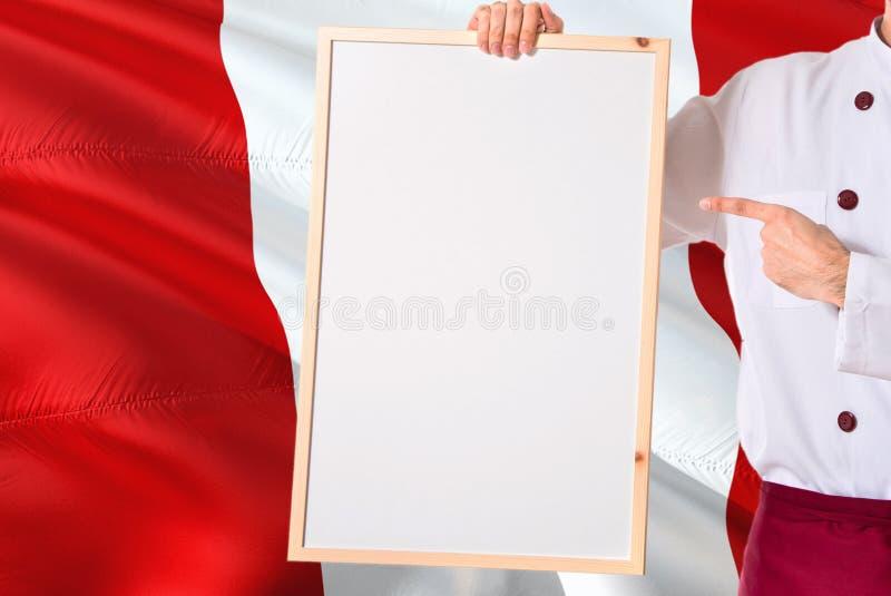 Chef péruvien tenant le menu vide de tableau blanc sur le fond de drapeau du Pérou Faites cuire l'uniforme de port dirigeant l'es image libre de droits