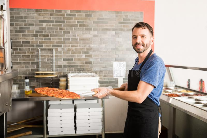 Chef with a pizza on a shovel in a kitchen of a restaurant stock photos