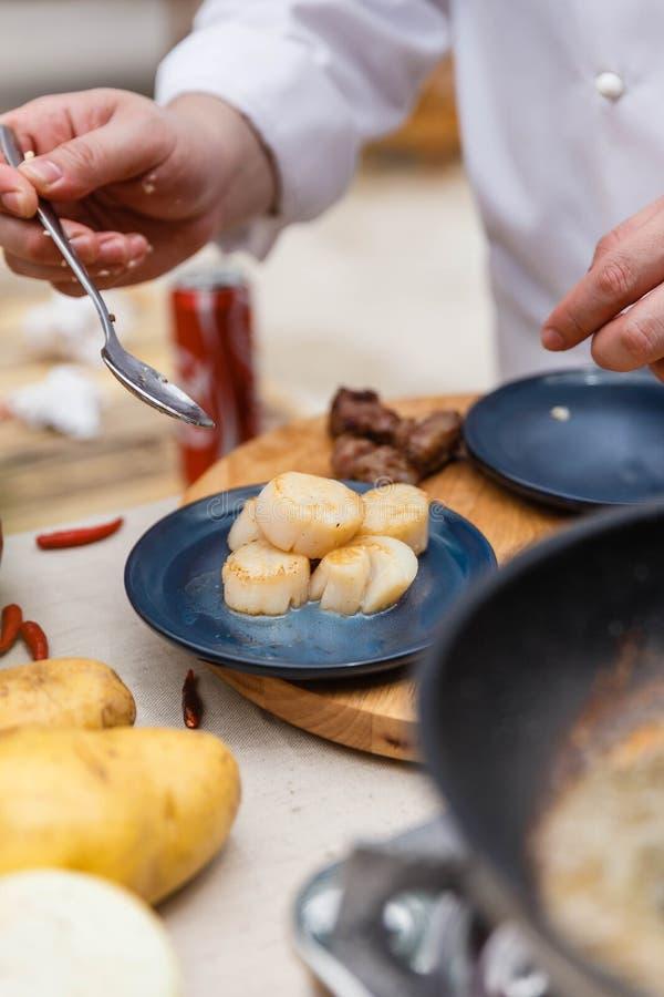 Chef Plating Fried Scallops in der blauen keramischen Platte lizenzfreies stockbild