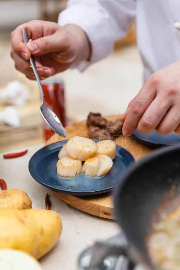 Chef Plating Fried Scallops in der blauen keramischen Platte lizenzfreie stockbilder