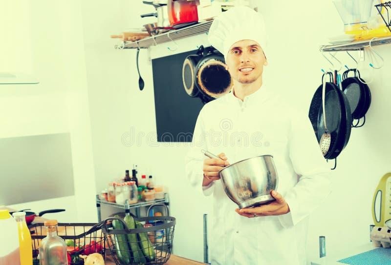 Chef positif de jeune homme faisant cuire la nourriture à la cuisine images stock