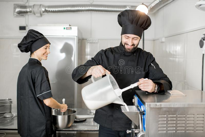 Chef cook making ice cream. Chef pouring basis into the ice cream freezer machine in the small manufacturing stock photography