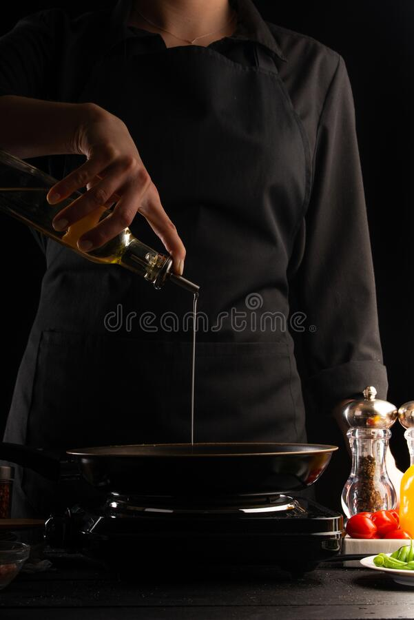 The chef pours oil in a pan for cooking. Freezing in motion. Delicious and healthy food. Vegetables and meat royalty free stock photography