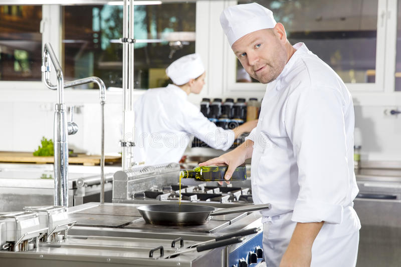 Chef pours olive oil in pan at a professional kitchen. Two chefs working in gourmet restaurant or hotel. Chef pours olive oil in a pan in a professional kitchen royalty free stock photography